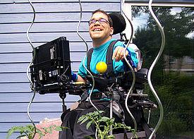 Ein erwachsener Mann im Rollstuhl steht im Garten neben einem Haus und lacht.