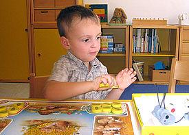 Ein kleiner Junge sitzt über einem Brettspiel an einem Tisch.
