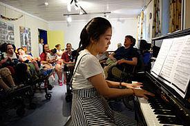Eine junge Frau spielt auf dem Klavier in einer Runde von Zuhörern.