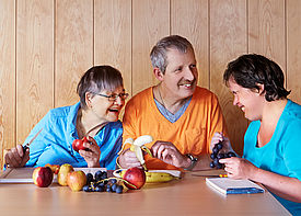Drei erwachsene Menschen mit Behinderung sitzen an einem Tisch und schneiden Obst.