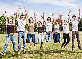 Acht junge Leute in Jeans und T-Shirt springen auf einer Wiese in die Luft.
