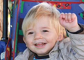 Ein kleiner Junge sitzt in einem Buggy und winkt.