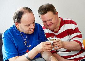 Zwei Männer mit Behinderung sitzen auf einem Sofa und stoßen gemeinsam an.