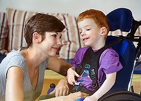 Ein kleiner Junge im Rollstuhl unterhält sich mit einer Betreuerin, die vor ihm sitzt.