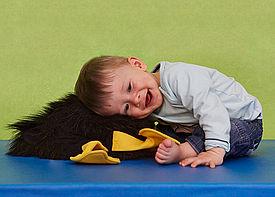 Ein kleiner Junge sitzt vorübergebeugt auf einer Behandlungsmatte und lacht.
