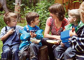 Vier Kinder und eine Erzieherin sitzen im Wald und vespern.