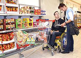 Ein Mann im Rollstuhl ist zusammen mit einer Assistenzkraft im Supermarkt einkaufen.