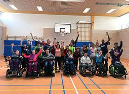 Eine Gruppe Jugendlicher und einige Sportler stehen in einer Sporthalle und winken.