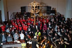 Musiker und Schülerchor befinden sich im Altarraum einer Kirche