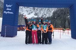 Sieben Personen in Schneekleidung stehen im Schnee und machen Siegerposen.