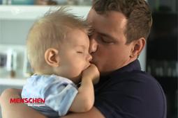 Ein Mann hält ein Baby in seinem Arm und kuschelt mit ihm.