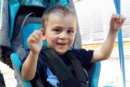 Ein Junge in einem Rollstuhl hebt die Arme und lächelt.