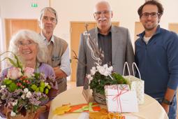 Vier Personen blicken lächelnd in die Kamera. Die Person ganz links hält einen Blumenstrauß.