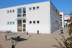 Außenansicht eines Schulgebäudes mit Pausenhof.