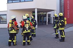 Sechs Feuerwehrleute stehen vor einem Gebäude.