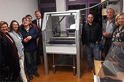 Eine Gruppe Männer und Frauen posiert neben einer neuen Fräsmaschine.