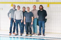 Eine Gruppe von sechs Personen steht am Rand eines Schwimmbeckens.