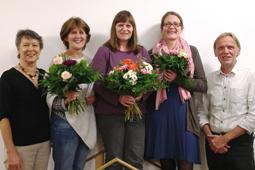 Eine Gruppe von fünf Erwachsenen lächelt in die Kamera. Drei von ihnen halten einen Blumenstrauß.
