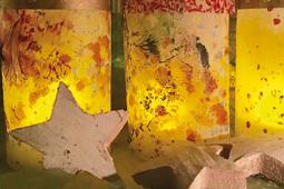 Vor drei bunt bemalten Leuchten aus Papier liegen drei Holzsterne.