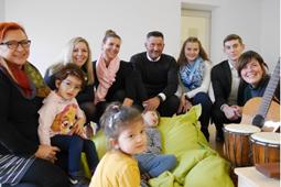 Sieben Erwachsene und drei Kinder sitzen auf dem Boden mit Musikinstrumenten.