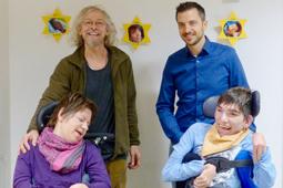Vier Personen, davon zwei im Rollstuhl, stehen vor einer Wand.