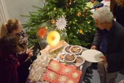 Ein Mann steht vor einem Verkaufsstand mit Torten, Plätzchen und Strohsternen. Im Hintergrund steht ein geschmückter Weihnachtsbaum.