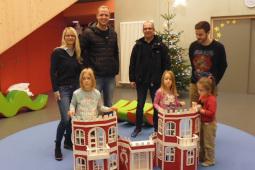 Vier Erwachsene und drei Kinder stehen hinter einem großen Spielhaus, das wie eine Burg gestaltet ist.