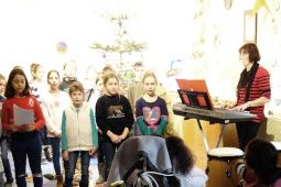 Eine Gruppe Schüler steht vor einem Weihnachtsbaum und singt. Links im Bild steht eine Lehrerin am E-Piano.