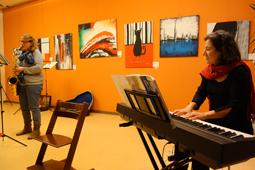 Eine Pianistin und eine Saxofonistin spielen ein Stück. Im Hintergrund hängen bunte Bilder an einer Wand.