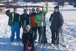 Sechs Personen mit Winterkleidung und Skiern stehen im Schnee.