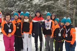 Eine Gruppe Schüler in Jacken und Mützen und ein Mann stehen im Schnee vor einem Tannenwald.