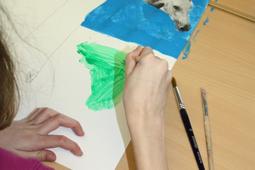 Eine Schülerin malt ein Bild mit einem Pinsel.