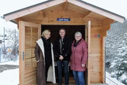 Drei Personen stehen vor einer Holzhütte.