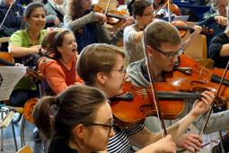 Ein Kind im Rollstuhl und eine Betreuerin sitzen mitten zwischen Jugendlichen, die Geige spielen.