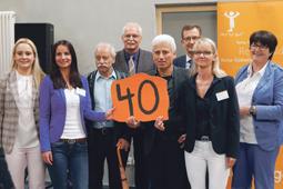 Acht Personen blicken in die Kamera. In der Hand halten sie ein Pappschild mit der Zahl 40.