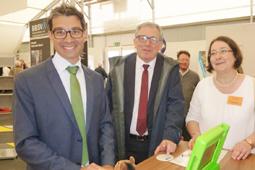 Zwei Männer und eine Frau stehen in einer Halle an einem Stand und lächeln.