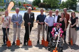 Auf dem Bild sind neun Erwachsene und ein Kind im Rollstuhl zu sehen. Sie stehen auf einer Baustelle, im Hintergrund ist ein Bagger zu sehen. Jeder hält einen Spaten in der Hand.