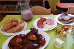 Auf einem Tisch stehen Teller mit Wurstwaren und Gebäck sowie eine Kanne mit einem Milchshake.