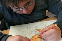Ein Junge mit einer Brille sitzt vor einem Blatt Papier. Er zeichnet einen Fisch.