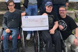 Zwei Jungen im Rollstuhl halten einen Spendenscheck in die Kamera. Neben ihnen sitzt ein Mitarbeiter.