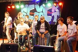 Acht junge Musiker musizieren auf einer Bühne.