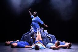 Eine Tänzerin steht auf der Bühne. Um sie herum liegen weitere Tänzer auf dem Boden.