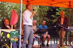 Ein Mann in einem feinen Hemd steht auf einer Bühne und spricht in ein Mikrofon. Im Hintergrund sind Leute an Instrumenten zu sehen.