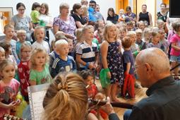Eine große Gruppe Kinder und einige Erwachsene singen ein Lied. Im Vordergrund ist ein Mann an einer Gitarre zu sehen.