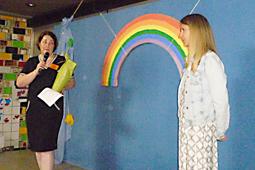 Zwei Frauen stehen auf einer Bühne, hinter ihnen befindet sich ein großer Regenbogen aus Pappe.