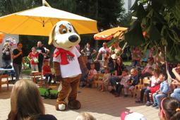 Ein als Plüschhund verkleideter Mensch steht auf einem Platz. Um ihn herum sitzen und stehen viele Kinder und Erwachsene.