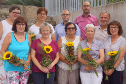 Zehn Erwachsene blicken in die Kamera. Einige von ihnen haben einen Strauß mit einer Sonnenblume in der Hand.