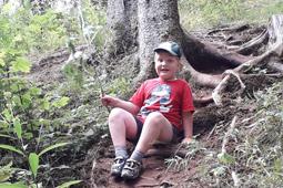 Ein Junge in kurzer Hose und Schirmmütze sitzt im Wald unter einem Baum.