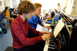 Zwei junge Männer spielen vierhändig Klavier.