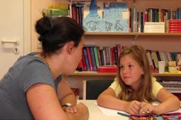 Eine Schulbegleiterin und ein Kind sitzen vor einem Bücherregal und schauen sich an.
